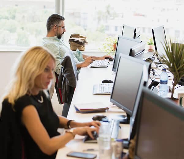Una mujer y un hombre programando en unos escritorios